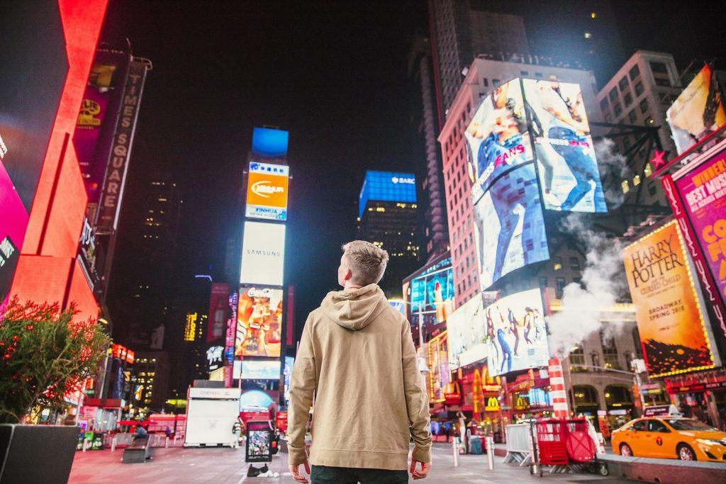 Reach vs Impressions: ilustrasi orang (1 reach) melihat banyak iklan billboard (banyak impression)